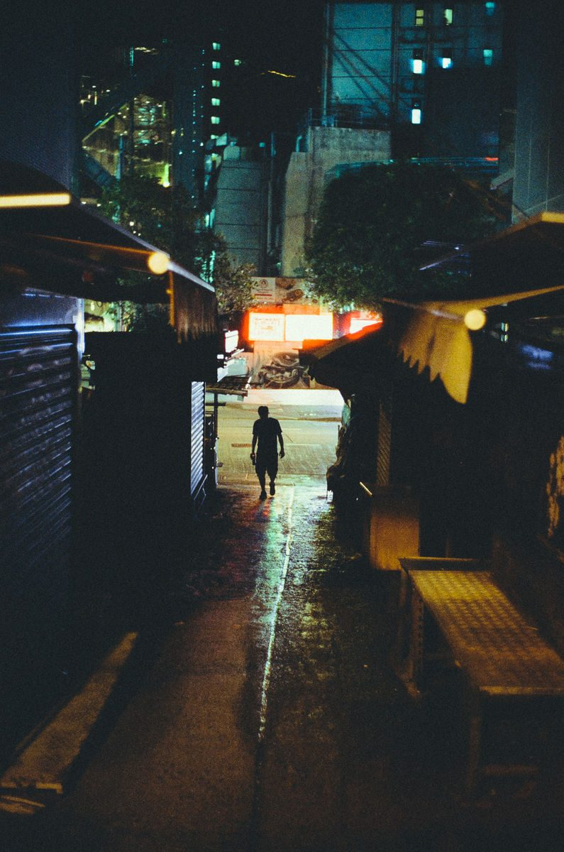 man alone in a dark street.