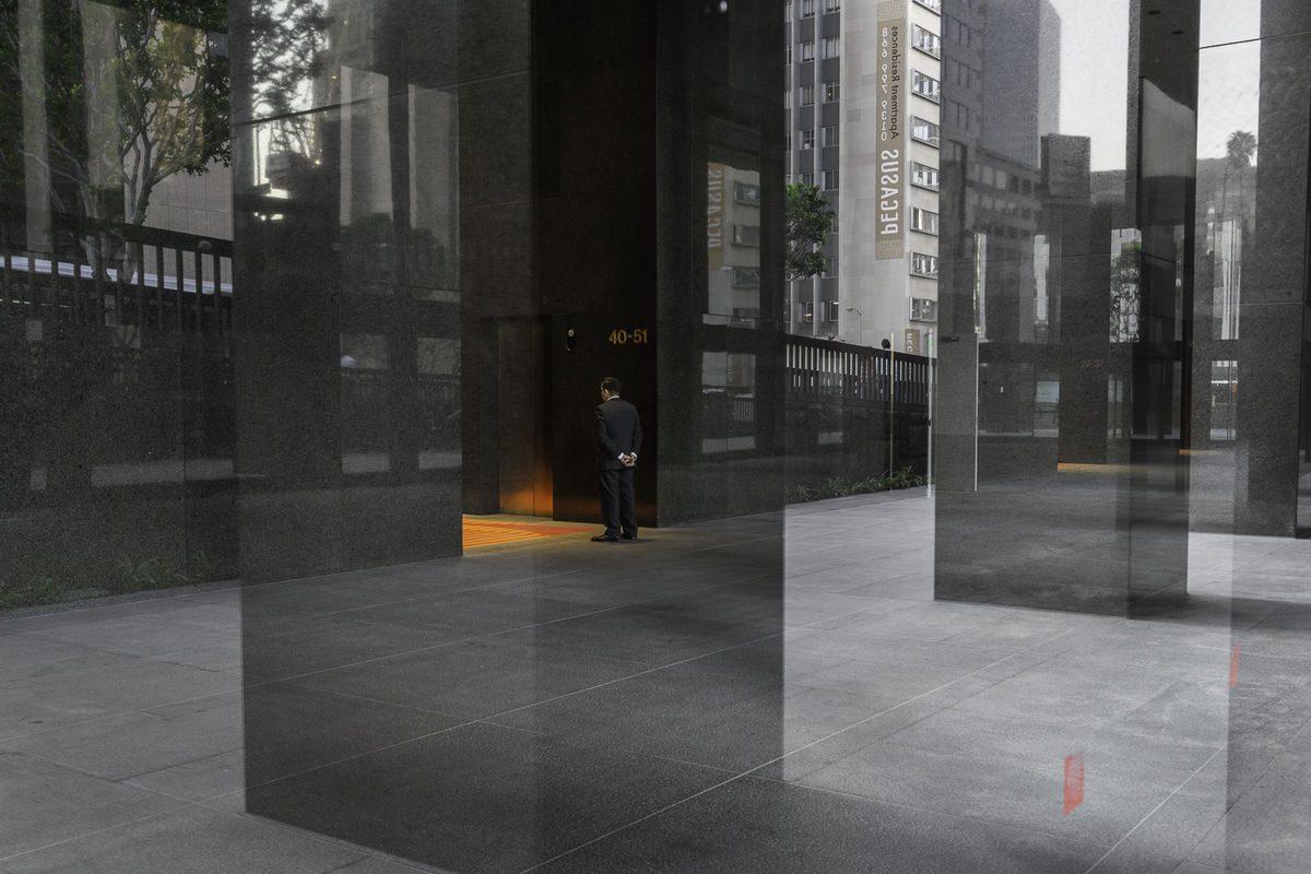 elegant man in front of a building entrance.