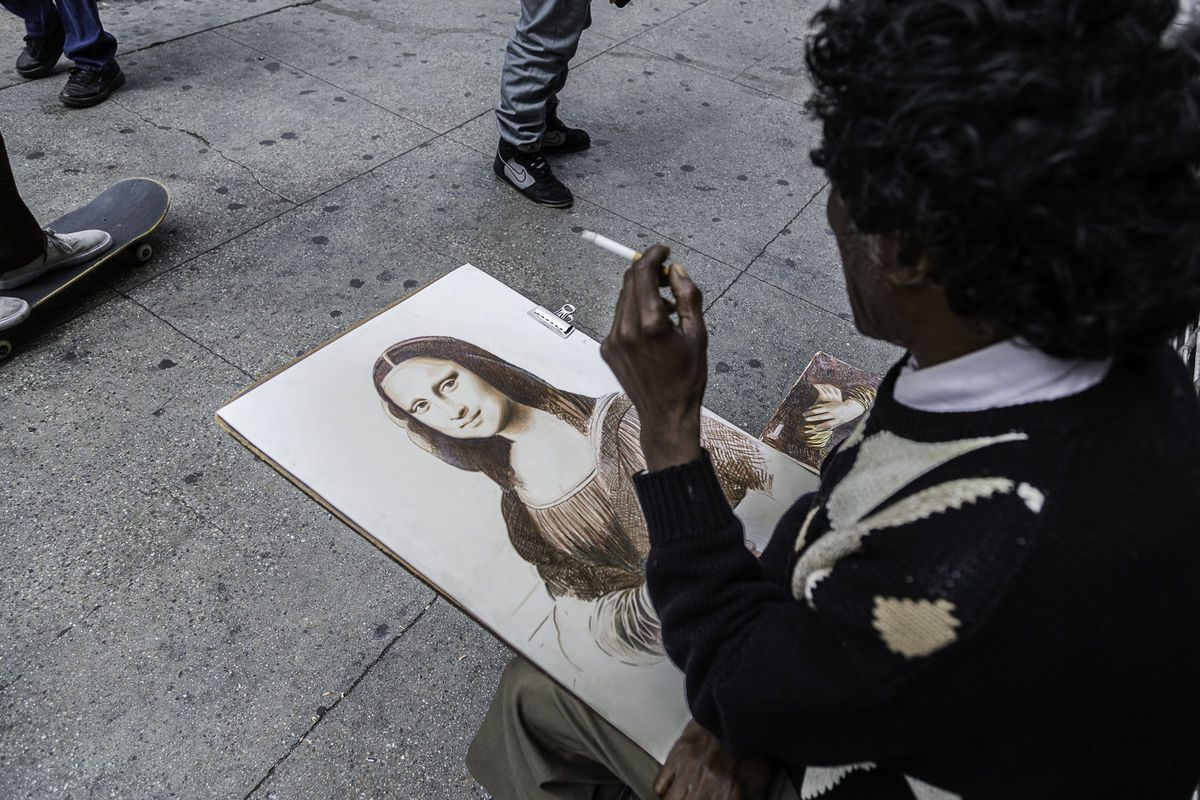 man with cigarette looks at Gioconda drawing.