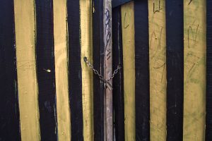 yellow and black striped gate with a chain