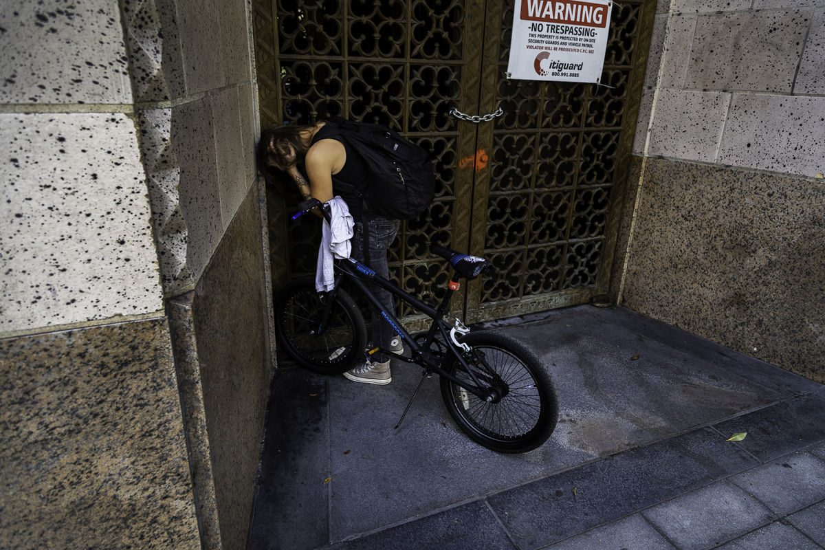 cyclist holds his hands in the corner of a doorway.