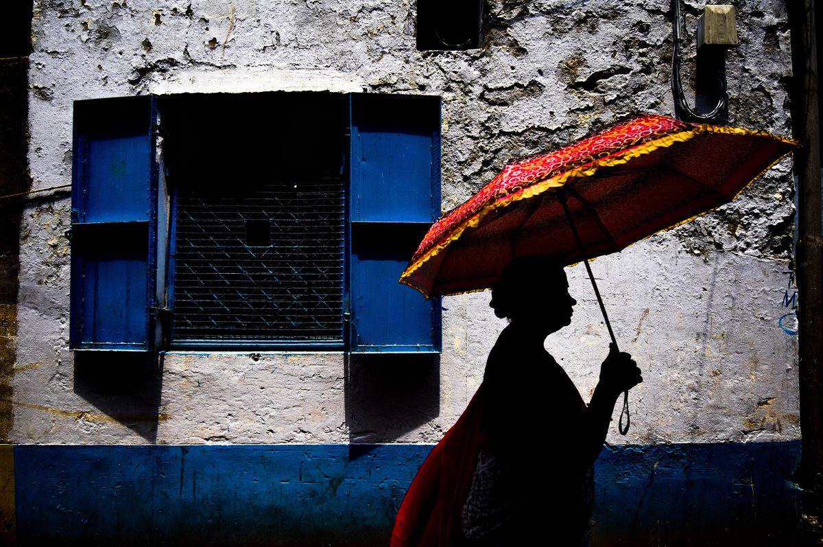 colourful streetswoman in shadow with umbrella